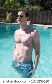 Athletic man standing in an outdoor swimming pool with defined abs. Healthy and active man posing in a pool water up to his waist on a summer day. Confident man in a backyard pool on warm sunny day.