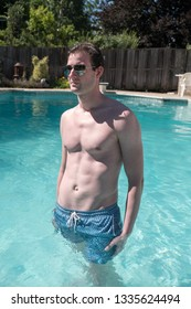 Athletic man standing in an outdoor swimming pool with defined abs. Healthy and active man posing in a pool water up to his waist on a summer day. Confident man in a backyard pool