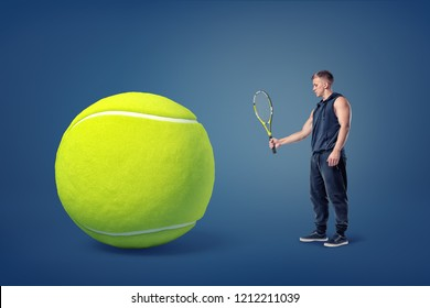 An athletic man stands in a side view holding a tennis racquet in front of a giant yellow ball. Tennis gear. Professional player. Personal competition.