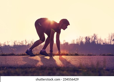 Athletic man starting evening jogging in sun rays