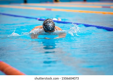 Athletic man swimming in Breaststroke style in the swimming pool with clear blue water. Triathlon fitness athlete training swimming.