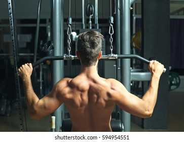 Athletic man training back muscles in gym