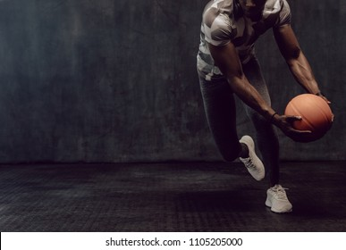 Athletic man training with a basketball. Man working out holding a basketball in hand.