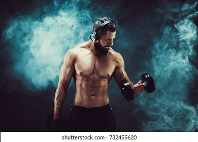 Athletic man training muscles with dumbbells in studio on dark background with smoke. Strong bodybuilder with six pack, perfect abs, shoulders, biceps, triceps and chest posing with headphones