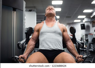 athletic man trains in the gym. Training of biceps