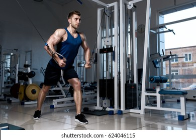 Athletic man in a T-shirt standing training on a exercise machine in the gym