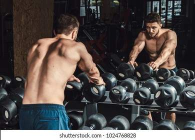 athletic man waiting and looking at himself before lifting dumbbells in front of the mirror