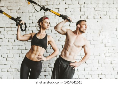 Athletic man and woman doing TRX workout at gym.