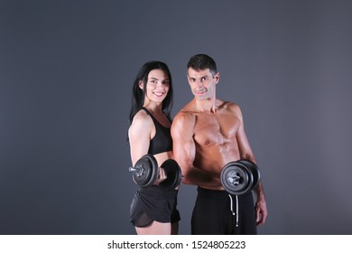 Athletic man and woman with dumb-bells. Personal fitness instructor. Personal training. Weight training. Workout.