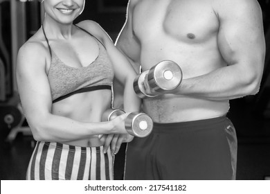 Athletic man and woman with a dumbells.Fitness, sport, training, gym and lifestyle concept - two smiling people working out with dumbbells in the gym.couple in the gym, exercising with dumbbells