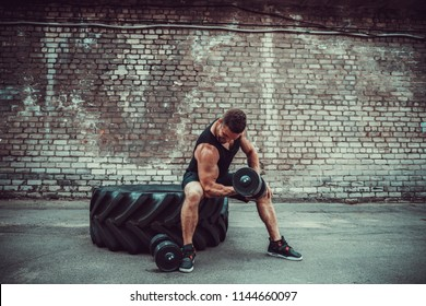 Athletic man working out with a dumbbell in front of brick wall while sit on big tire. Strength and motivation. Outdoor workout. Exercise for the muscles biceps