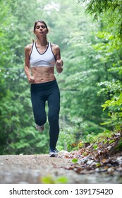 Athletic middle aged caucasian woman on a run in green leaved woods on a dirt road in Surry, Maine, USA during the Summer.