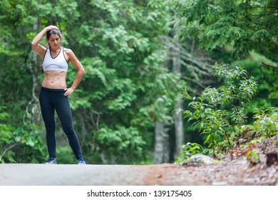 Athletic middle aged woman rests with her hands on her head and hips while on a run in green leaved woods on a dirt road in Surry, Maine, USA during the Summer.