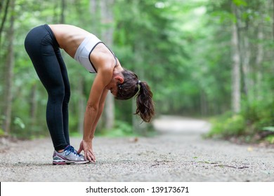 Athletic middle aged woman stretching in the green leaved woods on a dirt road before a run in Surry, Maine, USA during the Summer.