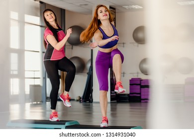 Athletic mother and daughter raising legs on step platforms