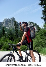 Athletic mountainbiker with a rucksack on his back pausing on his bicycle to look up at the mountain