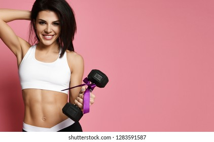 Athletic muscular fitness girl doing exercise for arms with big dumbbell working out on pink background. New spring sport workout concept for woman day 8 march