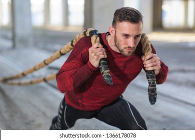 Athletic, muscular man doing a battle ropes functional training, pulling the ropes, exercising strength