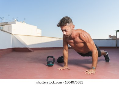 Athletic and muscular man doing push-ups during a fitness session  on the terrace of his home