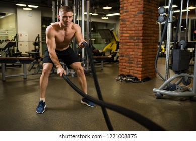 Athletic muscular man engaged with a thick rope with a bare torso in the gym.