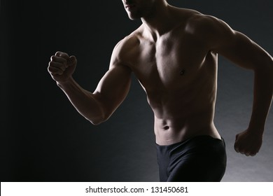 Athletic and muscular man is running