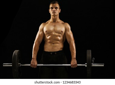 Athletic muscular young man holding barbell. Concept of training in the gym and functional training