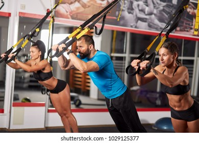 Athletic people doing crossfit training with suspension straps