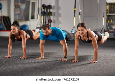 Athletic people doing crossfit training with trx straps