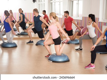Athletic people during bosu training at the gym