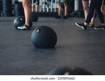Athletic people working out in an open gym environment. A weighted ball, called a slam ball sit in the foreground during a class.