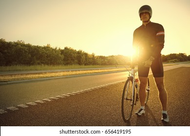 Athletic person with the bike standing and resting on empty highway in the evening.