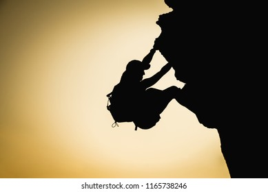 Athletic person silhouette climbing a vertical rock. Adventure and challenge concept