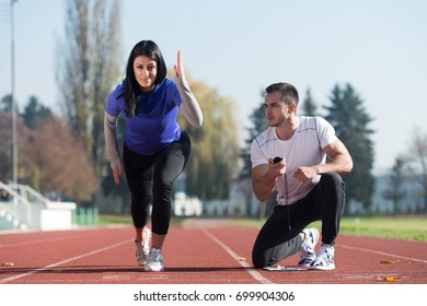 Athletic Personal Trainer Helping Female To Sprint on the Running Track in City Park Area - Training and Exercising for Endurance - Healthy Lifestyle Concept Outdoor