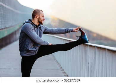 Athletic runner doing stretching exercise, preparing for morning workout in the park