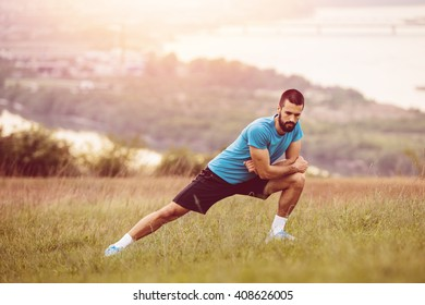 Athletic runner doing stretching exercise, preparing for running in the nature with the city in background. Healthy lifestyle