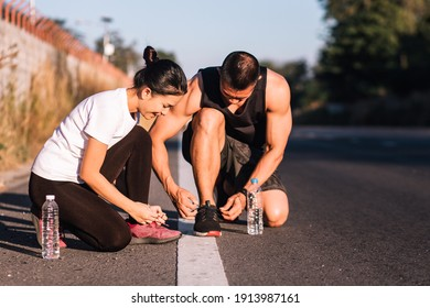 Athletic runner man and woman sitting and tying shoelaces before work out. Sportive happy couple preparing running on the road.