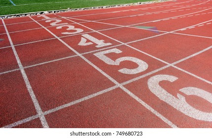 Athletic running red track, lane and numbers next to the green grass.