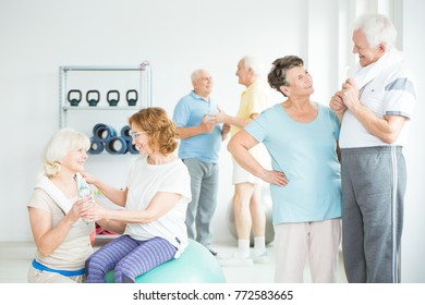 Athletic senior friends talking at a gym with equipment after classes