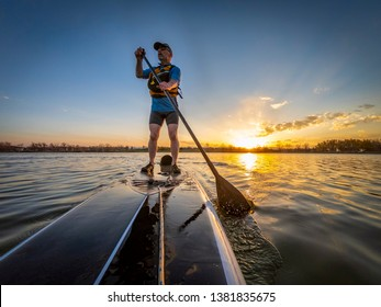 athletic senior man paddling a stand up paddleboard at sunset on a calm lake in Colorado, bow view