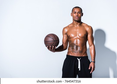 athletic shirtless african american man with basketball ball looking at camera on grey