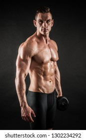 Athletic shirtless young male fitness model makes exercises with dumbbells on dark background