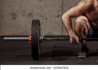 Athletic shirtless young man doing exercise with barbell in gym.close up cropped photo. focus on the barbell plate