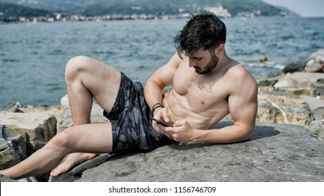 Athletic shirtless young man at the seaside using cell phone to type message while looking at the sea and beach