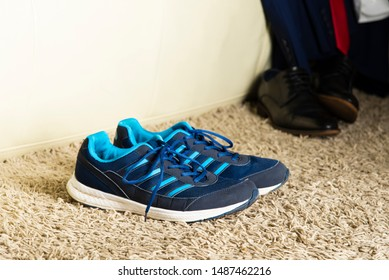 Athletic shoes stand next to the sofa next to a business suit