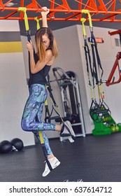 Athletic slim female fitness model in colorful sportswear exercising with trx suspension strips in a gym club.