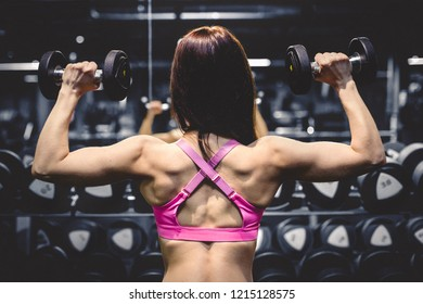 Athletic slim girl doing exercises with dumbbell in the gym. Sports concept. Working hard on a fat burning and a healthy lifestyle.