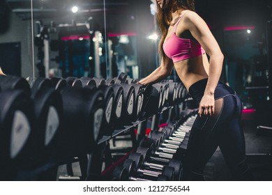 Athletic slim girl standing with dumbbell in the gym. Sports concept. Working hard on a fat burning and a healthy lifestyle.