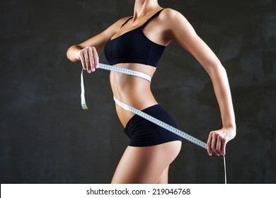 Athletic slim woman measuring her waist by measure tape after a diet over dark gray background