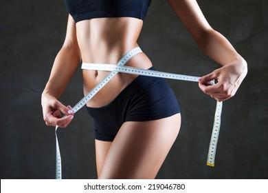 Athletic femeie subțire de măsurare talie cu bandă de măsură după o dietă pe fundal gri închis
