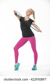 Athletic smiling blonde in the sportswear stands on the white background in the studio. She wears cyan-yellow sneakers, pink pants and black t-shirt. She pulls a skipping rope with her raised hands